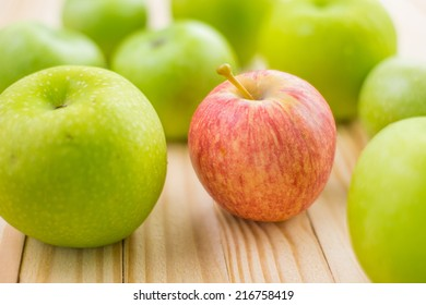 a red apple among green apples