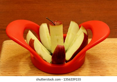 Red Apple cut and cored on a wooden cutting board