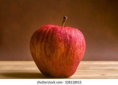 red apple with drop of water on skin put on wood table with brown background. Healthy fruit