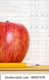 Red apple in front of a vintage report card