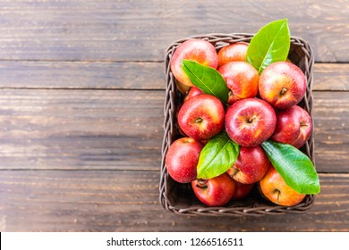 A lot of red apple fruit in brown basket on table