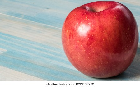 Red apple fruit over wooden pastel background