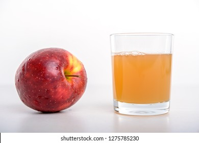 red apple with glass of naturally cloudy juice in front of white background