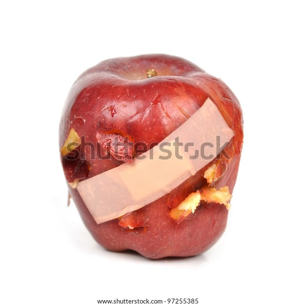 A red apple has a band-aid over with cut and bruised pieces on a white isolated background. Use it for an abuse or sickness concept.