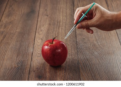 Red apple injecting a needle or syringe and chemical pesticides on a wooden background. Specific pesticide residues in apples, fruits and vegetables. Concepts of genetic modification. Products of GMOs