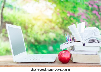 Red apple, laptop, book stack on wooden table in nature background