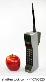 Red apple and large old brick style cell phone.