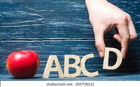 Red apple and letters ABCD. The hand puts the letter D in the alphabet order. Apple for the teacher. The concept of teaching and education. School, college, kindergarten, university. Primary school.
