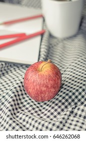 red apple and note book on fabric pattern background with retro filter