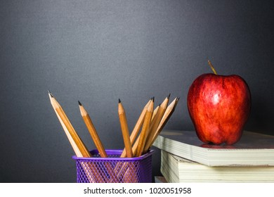 Red apple on book with Pencil and Blackboard (Chalk Board) as background. Education concept.