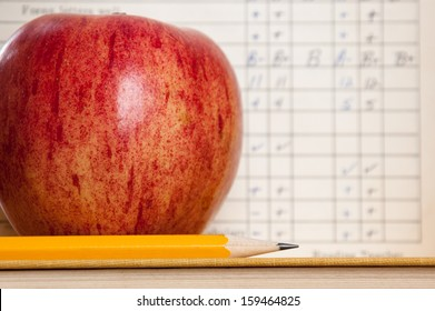 Red apple on a book with pencil and vintage report card in background