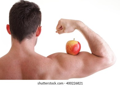 Red Apple on Man Bicep Muscle isolated on white. Athletic sexy male body builder holding