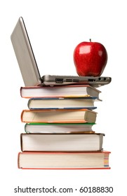 Red apple on top of computer and stack of school books.  Concept of education or back to school.
