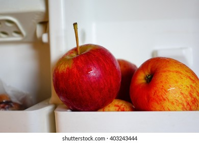 Red apple on white shelf in refrigerator:Close up,select focus with shallow depth of field.