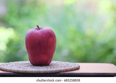 red apple on wooden table green bokeh background
