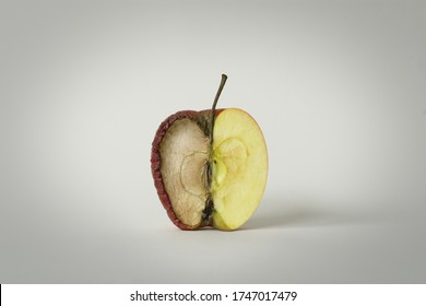 red apple with one half good and the other half rotten, concept of time, fruit that becomes garbage and that is thrown away, white background, isolated object