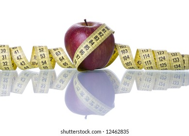 Red apple over a measure tape isolated on white with reflection