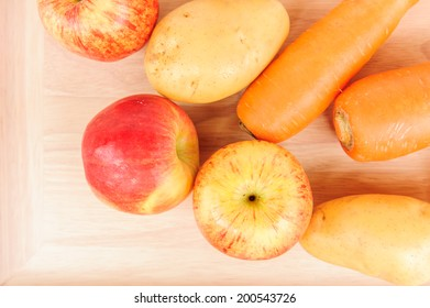 red apple, potato and carrot on wood board.