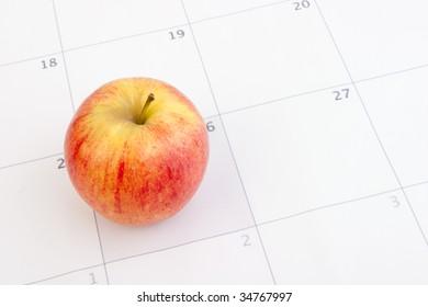 A red apple set on a calendar