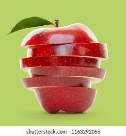 Red apple slices piled up and isolated on green background.