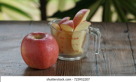 Red apple and apple slide in pieces put in a measure glass cup.