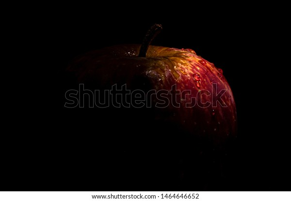 Red Apple sprinkled with water drops in dark setting with text space on left side