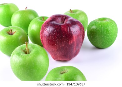 A red apple stands out as unique among a bunch of green apples