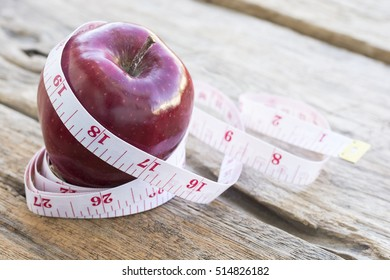 The red apple and  a tape measure placed on the wooden floor.