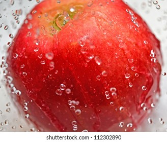 Red apple in water splash close up