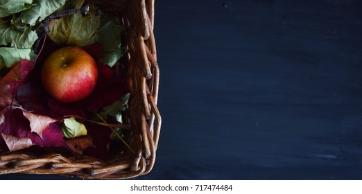 red Apple in a wicker basket in the autumn leaves