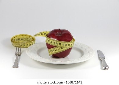 Red apple with yellow metric tape around