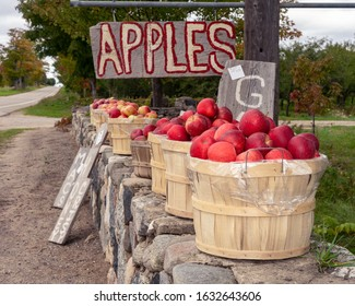 Red apples in a basket with a hand painted apple sign.  Gala, Honey crisp, Macintosh apples. sitting on a stone wall in Northern Michigan.  Road side stand.  Organic. Healthy option food.