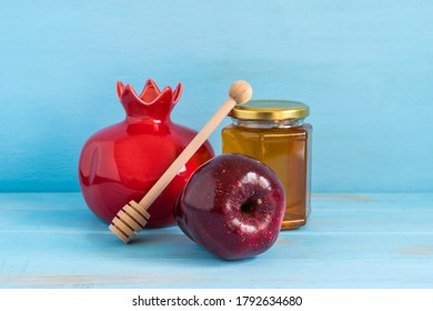 Red apples and fresh honey for Jewish holiday Rosh hashana on blue wooden background.