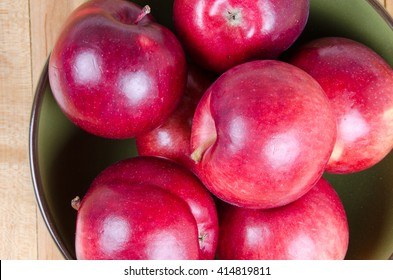 Red apples in a green bowl on a wood floor