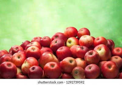 Red apples heap isolated on green background
