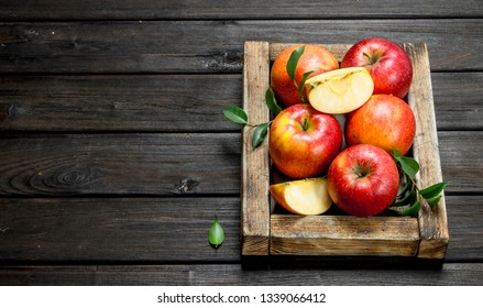 Red apples with leaves and Apple slices in a wooden box. On a dark wooden background.
