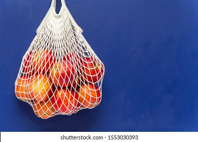 Red apples in a mesh cotton bag blue background