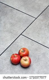 red apples, on grey floor tiles with black seams