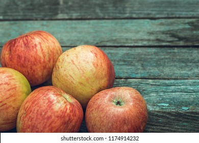 Red apples on old wooden table with copy space, toned