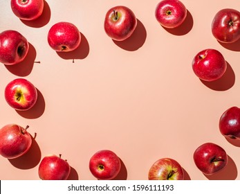 Red apples on orange or coral pink background with copy space for text or design in center. Colorful fruit frame. Creative concept. Flat lay or top view, Hard light