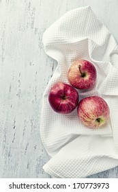 Red apples on a white tea towel. Concept for healthy nutrition. Bright wooden background. Top view. Copy space.