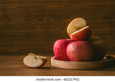 Red apples on the wooden table background.
