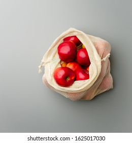 Red apples in a reusable grocery white cotton bag on a gray background. Top view.