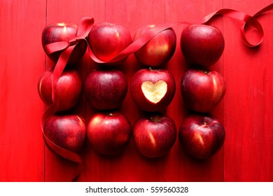 Red apples with red ribbon on red background