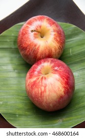 Red Apples two on with banana leaves