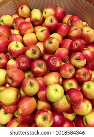 a lot of red apples in wooden box and brown paper in supermaket for sell.