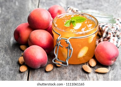 Red apricot  jam with almonds in a clear glass jar on wooden table