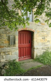 Red Arched Door Entrance in stone church with tree branches