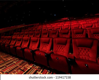 Red arm chair in dark theater