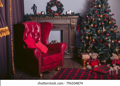 Red armchair in a modern style in the New Year's interior with a Christmas tree, a fireplace and gift packages